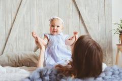 愉快的母亲和9个月大婴孩使用在卧室的配比的睡衣的早晨 免版税库存照片
