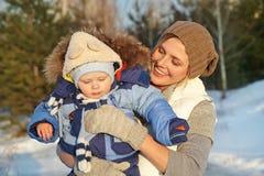 愉快的母亲和婴孩在冬天公园 免版税库存照片
