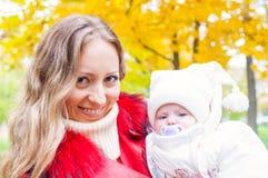 愉快的母亲和婴孩在秋天公园 免版税库存图片