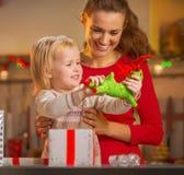 愉快的母亲和婴孩开头圣诞节礼物 免版税库存照片