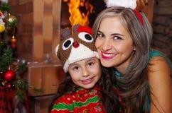 愉快的母亲和daugher在圣诞节,佩带鹿帽子和妈妈的litle女孩圣诞节帽子,有一室内chimmey的 库存图片