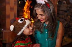 愉快的母亲和daugher在圣诞节,佩带鹿帽子和妈妈的litle女孩圣诞节帽子,有一室内chimmey的 图库摄影
