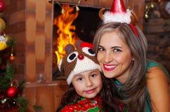 愉快的母亲和daugher在圣诞节,佩带鹿帽子和妈妈的litle女孩圣诞节帽子,有一室内chimmey的 免版税库存图片