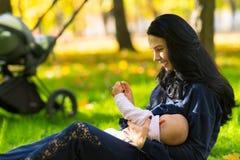 愉快的母亲哺乳的婴孩在城市公园土地 免版税库存图片