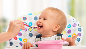 愉快的母亲喂养从匙子的滑稽的婴孩 库存图片