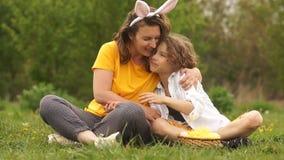 愉快的母亲拥抱儿子 家庭周末在公园 作为复活节兔子打扮的妈妈 愉快的复活节家庭 r 股票录像