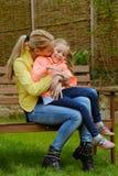 愉快的母亲拥抱室外她的女儿 库存图片