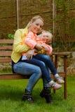 愉快的母亲拥抱室外她的女儿 免版税库存照片