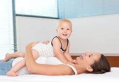 愉快的母亲拥抱的逗人喜爱的婴孩在床上 免版税库存照片