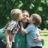 愉快的母亲的片刻!亲吻妈妈的两个儿童儿子 免版税库存照片