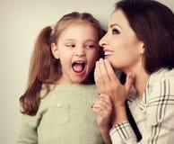 愉快的母亲耳语秘密对她惊奇的逗人喜爱的女孩我 库存照片