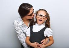 愉快的母亲耳语秘密对她激发在时尚玻璃的孩子与在空的拷贝空间的张的嘴 免版税库存照片