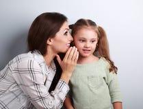 愉快的母亲耳语秘密对她耳朵的w逗人喜爱的孩子女孩 库存图片
