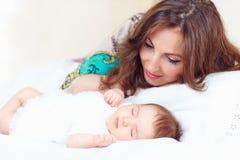 愉快的母亲近的睡觉的女婴 免版税图库摄影