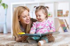 愉快的母亲读了一本书给儿童女孩户内 库存照片