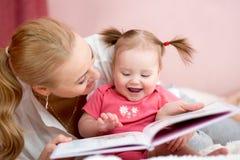 愉快的母亲读了一本书给儿童女孩 免版税库存图片