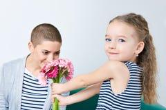 愉快的母亲` s天,妇女` s天或生日背景 给桃红色大丁草雏菊的妈妈花束逗人喜爱的小女孩 免版税图库摄影