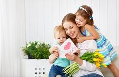 愉快的母亲` s天!孩子祝贺妈妈并且给她a 免版税图库摄影