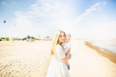愉快的母亲huges婴孩 母亲抱她的胳膊的孩子,拥抱妈妈的婴孩 免版税库存照片