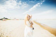 愉快的母亲huges婴孩 母亲抱她的胳膊的孩子,拥抱妈妈的婴孩 免版税库存图片