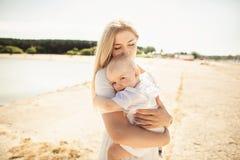 愉快的母亲huges婴孩 母亲抱她的胳膊的孩子,拥抱妈妈,特写镜头的婴孩 免版税库存图片