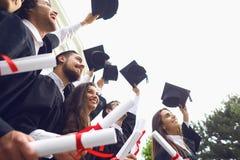 愉快的毕业生举了他们的有文凭纸卷的手  库存照片