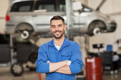 愉快的汽车机械师人或匠在汽车车间 免版税库存照片