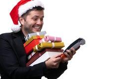 愉快的浅黑肤色的男人的图片圣诞老人的盖帽的有有礼物的箱子的,与终端 库存照片