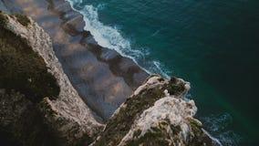 愉快的浪漫坐在著名诺曼底岸峭壁顶部的夫妇观看的日落海惊人的电影空中射击  影视素材