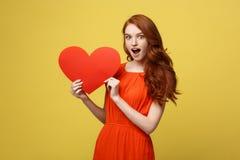 愉快的浪漫年轻白种人女孩画象有红色纸心形的明信片的,浪漫愿望,情人节 库存照片