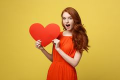 愉快的浪漫年轻白种人女孩画象有红色纸心形的明信片的,浪漫愿望,情人节 图库摄影
