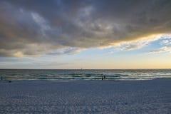 愉快的海上的夫妇观看的风船在海滩的日落期间 免版税库存照片