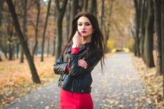 年轻愉快的深色的女孩红色唇膏秋天时兴的画象户外在城市 图库摄影