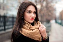 年轻愉快的深色的女孩红色唇膏秋天时兴的画象户外在城市 免版税库存照片