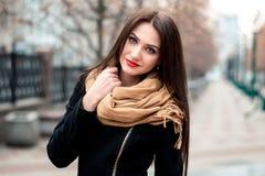 年轻愉快的深色的女孩红色唇膏秋天时兴的画象户外在城市 免版税图库摄影