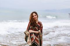 愉快的深色的妇女画象海滩佩带的雨披的 免版税库存照片