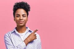 愉快的深色皮肤的混合的族种女性模型水平的画象表明与食指在空白的拷贝空间,展示 库存照片
