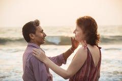 愉快的混合的族种夫妇临近海滩在日落 免版税图库摄影