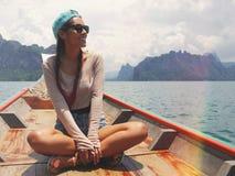 年轻愉快的混合的族种女孩开会和放松在Khao Sok湖的传统泰国木长尾巴小船 Phang Nga 免版税库存照片