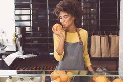 愉快的混血儿女孩在有机食品商店工作 图库摄影