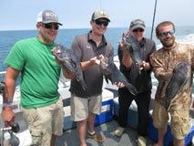 愉快的渔夫和他们的抓住 库存图片