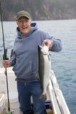 愉快的渔夫在阿拉斯加拿着大银色三文鱼 免版税库存图片