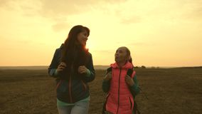 愉快的游人妈妈和女儿去与在平原的背包 在假期旅行的家庭 体育家庭的概念 股票视频