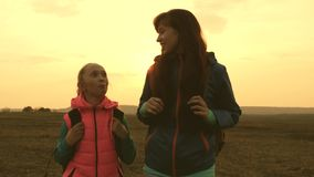 愉快的游人妈妈和女儿去与在平原的背包 在假期旅行的家庭 体育家庭的概念 股票录像
