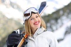 愉快的滑雪者看在山的照相机 免版税库存图片