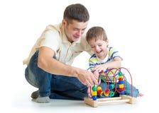愉快的演奏玩具的孩子男孩和爸爸 免版税图库摄影