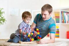 愉快的演奏玩具的孩子男孩和爸爸 图库摄影