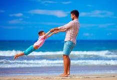 愉快的激动的使用在夏天的父亲和儿子使,享有生活靠岸 免版税图库摄影