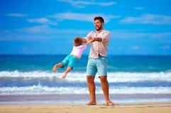 愉快的激动的使用在夏天的父亲和儿子使,享有生活靠岸 免版税库存图片