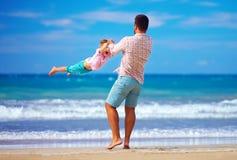 愉快的激动的使用在夏天的父亲和儿子使,享有生活靠岸 库存照片